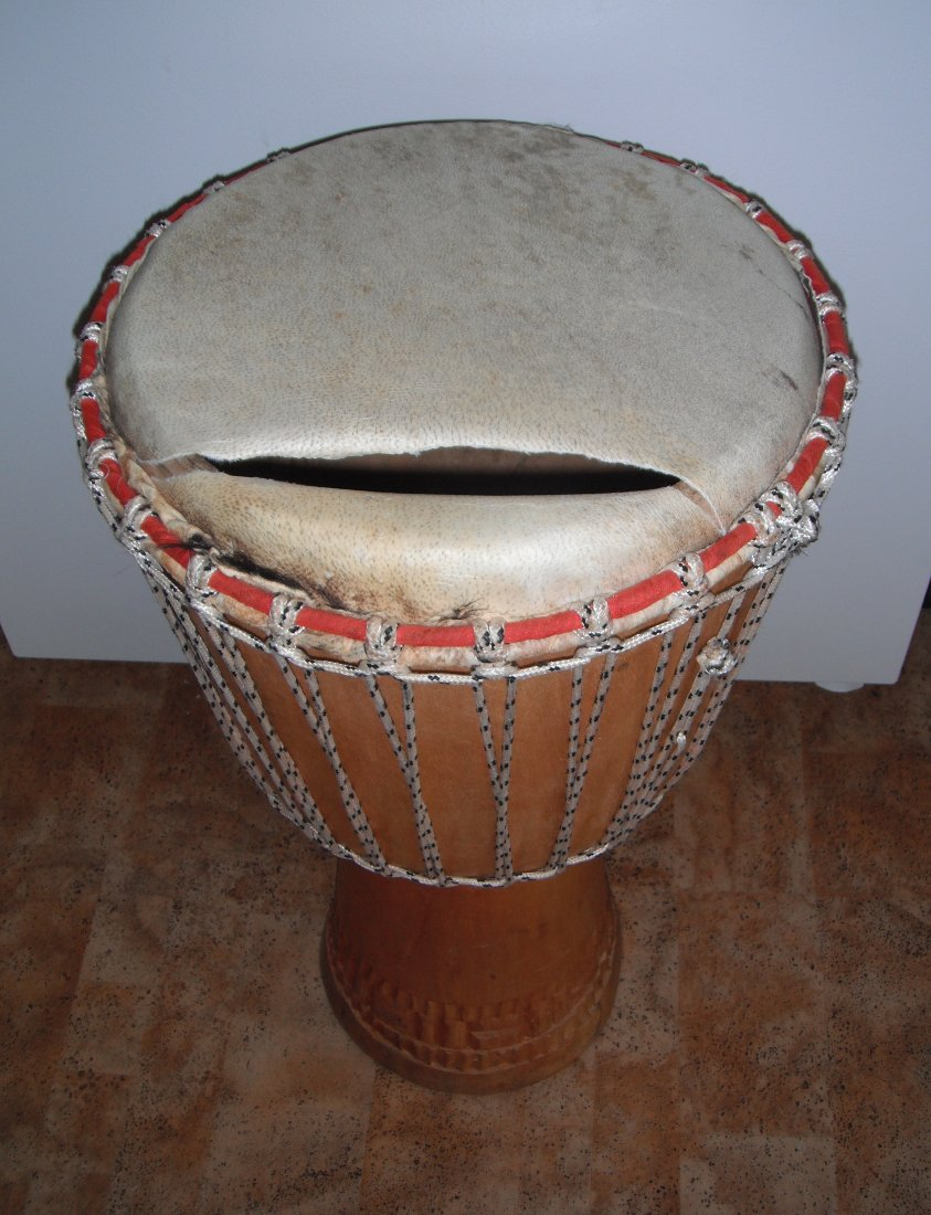 djembe hand drum with a torn skin. Black Bedroom Furniture Sets. Home Design Ideas