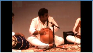 Sitting musician playing the ghatam.