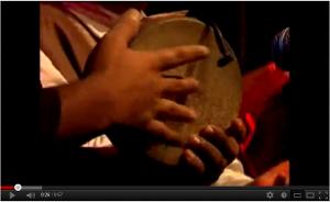 Sitting musician playing the kanjira.
