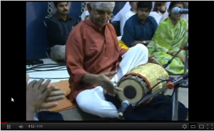 Sitting musician playing the mridangam.