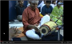 Sitting musician playing the mridangam.