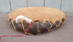 Native American medicine drum with broken lacing and damaged frame.