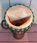 Stave djembe with a torn goat skin drum head.